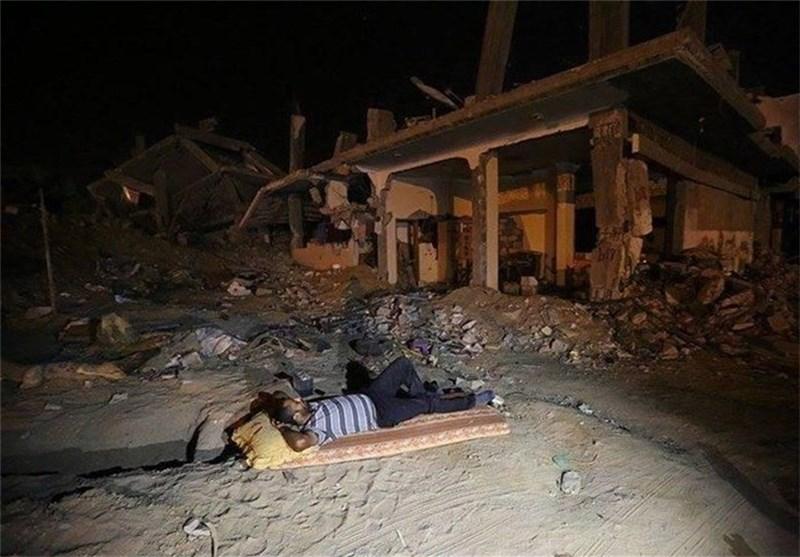 شاب فلسطینی ینام امام منزله المدمرفی العدوان على غزة