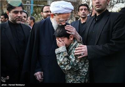 فرزند شهید مدافع حرم محسن فرامرزی در آغوش آیتالله محمد امامی کاشانی