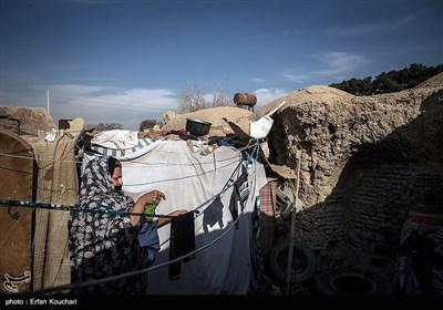 یکی از زنان روستا در حال پهن کردن لباس های شسته شده بر رو روی طناب است.