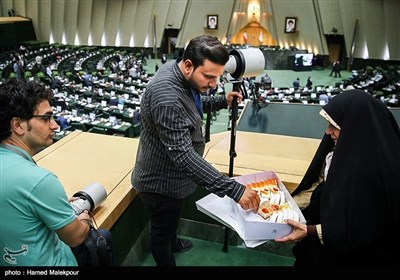 پخش شیرینی توسط یکی از نمایندگان مجلس به مناسبت روز خبرنگار
