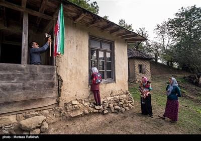 سمت چپ حمید عسکری نژاد یکی از اهالی روستا پرچم ایران که معلم با خود آورده بود را بر روی یکی از ستون های مدرسه نصب میکند. مادر امیررضا و آرزو دو دانش آموز مدرسه در حال تماشای آرزو هستند که با ذوق از پنجره کلاس به داخل نگاه میکند