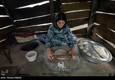 بهاره 40 ساله در حال آماده کردن خمیر نان برای قراردادن در تنور است. او در هر بار پخت 35 تا 40 نان میپزد که نیاز آنها به نان را تا سه روز برطرف میکند