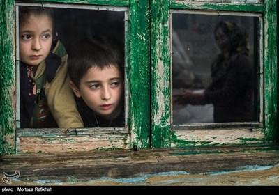 سونیا و سامیار شجاعی 7و5 ساله از داخل پنجره خانه به مادر خود که بیرون از خانه در حال شستن ظروف است نگاه میکنند. شستشوی ظروف و لباس در اکثر خانه ها بیرون از خانه انجام میشو که در فصل های سرد سال کار بسیار دشواری است