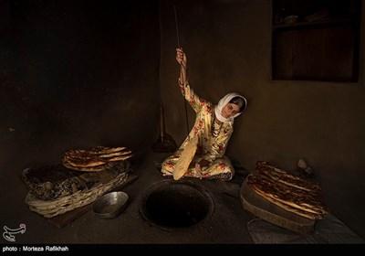 گلزار دشتی 60 ساله نان محلی که در زبان محلی به آن (پنجه قاش) میگویند را از تنور بیرون می آورد و برسی میکند تا کاملا پخته شده باشد