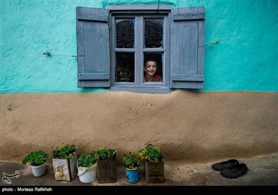 ساسان ذکریایی 9 ساله از پشت پنجره خانه اش به دوربین نگاه میکند