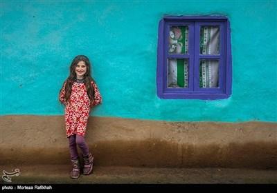 نازیلا خندان 8 ساله به دیوار خانه خود تکیه داده و در حالی که لبخند به لب دارد به دوربین نگاه میکند