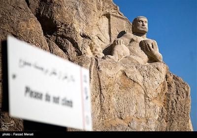 پیکره هرکول شخص قویهیکل را به نمایش میگذارد،این مجسمه در اثر احداث جاده از همدان به کرمانشاه در دامنه کوه کشف شد. سر هرکول یکبار به سرقت رفت، اما بعد از چند سال کشف و دوباره بر سر هرکول قرار داده شد. کتیبهای از زمان سلوکیان در پشت تندیس هرکول قرار دارد.