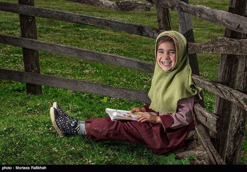 فاطیه عاقبتی 7 ساله دانش آموز پایه اول مدرسه عشایری مصباح روستای سیه پشت، در حالی که در حیاط مدرسه نشسته به دوربین لبخند میزند