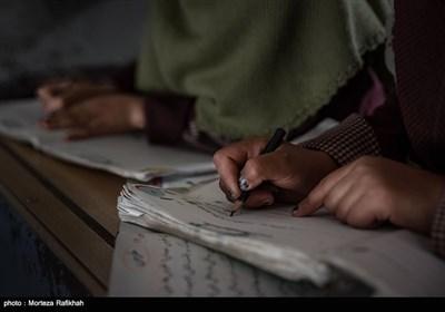 اسما قدمتی و فاطیه عاقبتی دانش آموزان کلاس اول مدرسه عشایری مصباح روستای سیه پشت، در کلاس درس از روی کتاب فارسی رونویسی میکنند