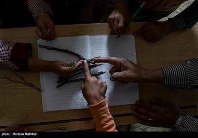 افشین تصوفی معلم مدرسه عشایری مصباح روستای سیه پشت، از شاخه درختان به عنوان وسایل کمک آموزشی در درس ریاضی به دانش آموزان استفاده میکند