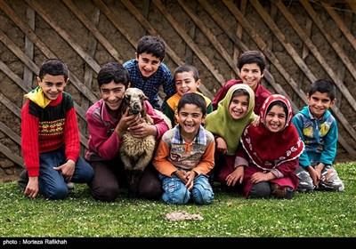 دانش آموزان مدرسه عشایری روستای سیه پشت، در حالی که در حیاط مدرسه نشسته اند برای ثبت عکس یادگاری به دوربین لبخند میزنند