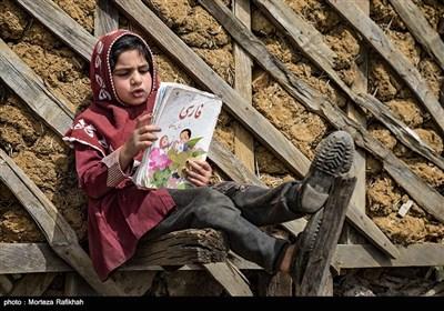 اسما قدمتی 7ساله دانش آموزپایه اول مدرسه عشایری مصباح روستای سیه پشت، در حیاط مدرسه درحالی که به دیوار مدرسه تکیه داده مشغول روخوانی یکی از درس های کتاب فارسی است