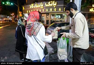 تعدادی از جوانان تهرانی در طول ماه مبارک رمضان اقدام به تهیه و توزیع بسته های افطاری ساده در سطح شهر تهران می کنند