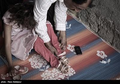 پدر در حال پوشاندن کفش های فاطمه ،این کودکان توانایی انجام کارهای شخصی خود را ندارند.