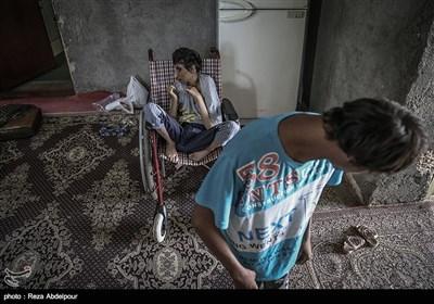 محمد علی نشسته روی ویلچر ،و خوبیار در حال بازی