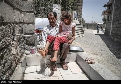 پدر در حال شستن پاهای فاطمه ،این کودکان توانایی انجام کارهای شخصی خود را ندارند.