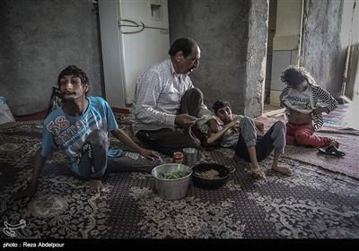 پدر در حال کمک به مادر برای دادن غذا به بچه ها می باشد