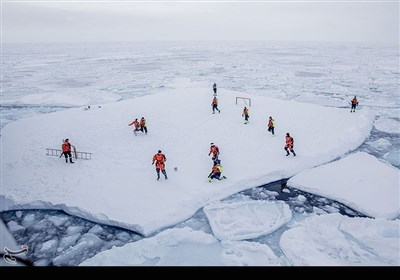 خدمه کشتی یخ شکن اسوالبارد که متشکل از سربازان و دانشمندان نروژی است در حالی که توسط افراد مسلح از خطر خرس قطبی محافظت شدهاند در حال فوتبال بازی کردن هستند.