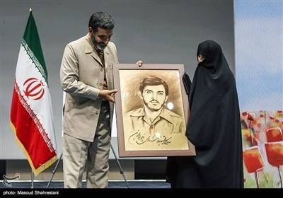 اهدای نقاشی شهید زین الدین به همسر شهید توسط حاج حسین یکتا در در مراسم رونمایی از کتاب(مربع های قرمز)