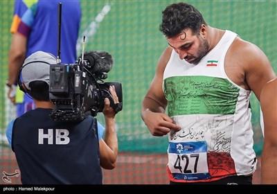 احسان حدادی شعر نوشته شده بر روی پیراهن خود را به تصویربردار مسابقات نشان میدهد
