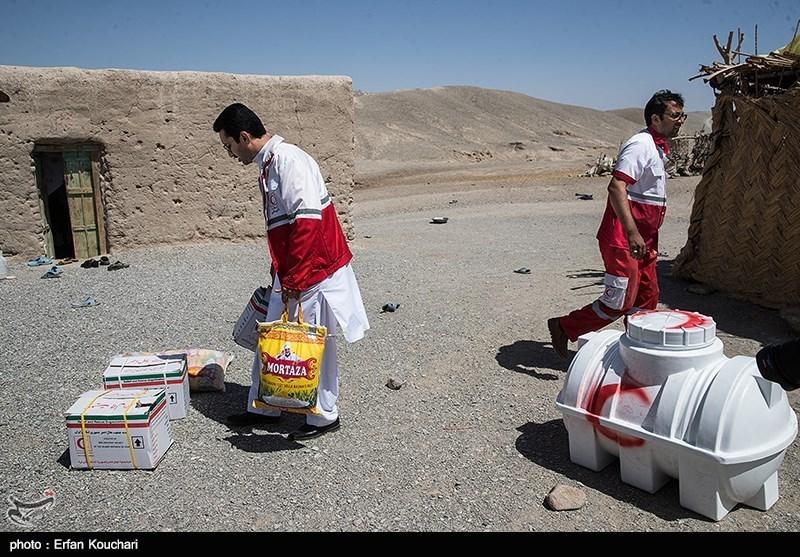 سازمان هلال احمر حین سرکشی به مناطق برای تحویل تانکرها بسته کمکی ارزاق به خانواده های نیازمند اهدا می کند.