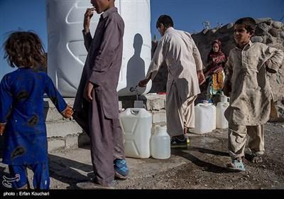 کودکان در حال پر کردن ظرف های آب خانوار خود هستند.