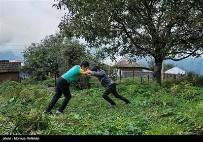از راست ساسان محرمی و محمدرضا محرمی در ساعت تفریح داخل حیاط مدرسه بازی میکنند.