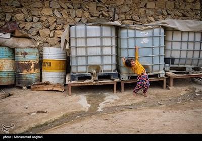 روستای کیش-بخش-ذلقی شرقی-شهرستان الیگودرز-استان لرستان-سارینا 3 سال و 4 ماهه در حال بازی با مخازن نگهداری آب در پشت خانه است.