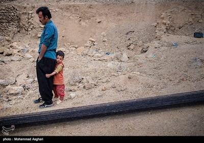 روستای پزعلیا-بخش ذلقی غربی - شهرستان الیگودرز-استان لرستان-محمد رضا حسنی4 ساله به همراه پدرش در کنار نخ های کشیده شده برای بافتن چادر سیاه.