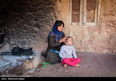 روستای درچین- بخش لقی غربی -شهرستان الیگودرز-استان لرستان-سارینا آراسته 6 ساله مادر سارینا مو های او را شانه و در حال بستن است.