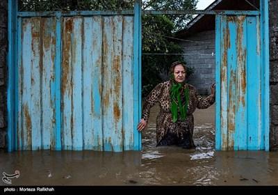 مهری نامور 61 ساله، در حالی که مقابل در ورودی خانه اش ایستاده به حجم آبی که واردخانه میشود نگاه میکند. خانه او که به همراه همسرش در آن زندگی میکند بر اثر جاری شدن سیل و ورود آب به داخل اتاق ها دچار خسارتهای بسیار زیادی شده. او میگوید اداره بیمه قبول نمیکند ما خانه مان را بیمه کنیم، چون احتمال وقوع سیل در این منطقه بسیار زیاد است. روستای چینی جان رودسر 14 مهر 97