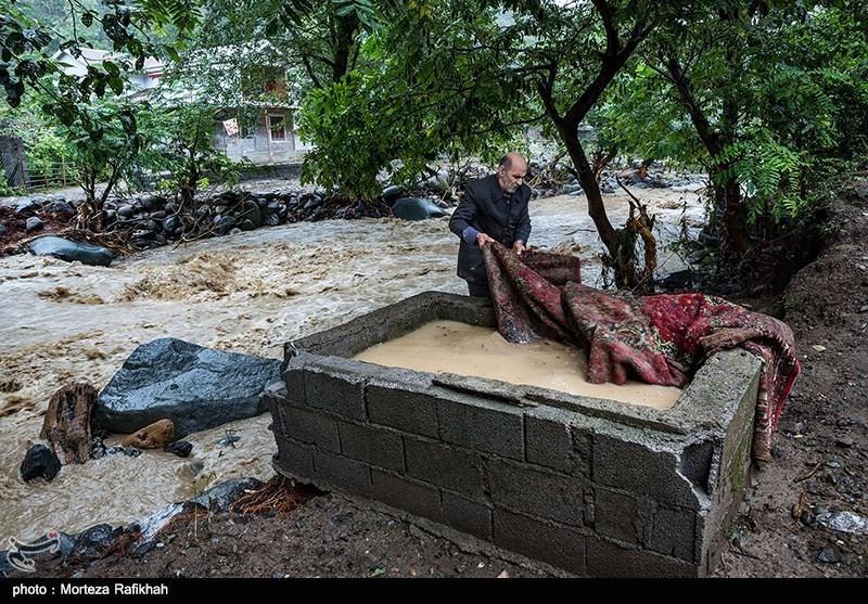رضاقلی پورخانعلی سعی میکند چند تکه فرش پاره ای که از کل وسایل زندگی، برایش به جامانده از داخل حوض آب بیرون بکشد. روستای خرجگیل تالش 6 مهر 97