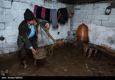محرمعلی شادکام در حال برسی لوازمی که بعد سیل در انبار خانه اش باقی مانده، است. تقریبا همه مواد غذایی که او برای مصرف سالیانه خود و خانواده اش ذخیره کرده بود از بین رفته. روستای خرجگیل تالش 6 مهر 97