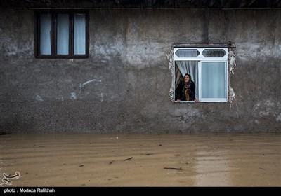 بتول رحیمی 52 ساله، از پنجره خانه اش به بیرون نگاه میکند.او امیدوار است تا با قطع شدن بارش باران از ارتفاع آبی که در حیاط خانه اش جمع شده کاسته شود و آب به داخل اتاقها نفوذ نکند. روستای چینی جان رودسر 14 مهر 97