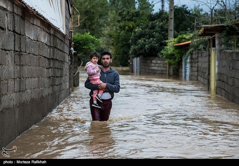پوریا عشوری 31 ساله، در حالی که دخترش حلما را در آغوش گرفته میان کوچه های محل زندگیش که از آب پر شده قدم میزند. او میگوید 5 صبح متوجه وقوع سیل شده و نتوانست وسایل های منزل را به جای امنی انتقال دهد تا از شدت خسارتها بکاهد. روستای میان پشته رودسر 14 مهر 97