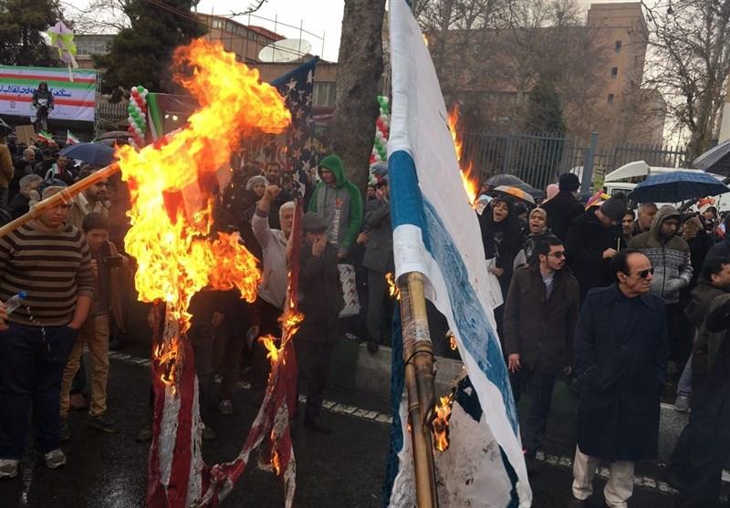 احتفال الذکرى الاربعین لانتصار الثورة..المشارکون فی طهران یحرقون العلمین الأمریکی والصهیونی