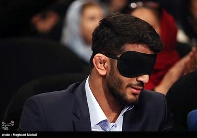 حسن یزدانی قهرمان کشتی جهان به پیشنهاد خبرنگار خبرگزاری صدا و سیما چشم بند بر صورت خود گذاشت