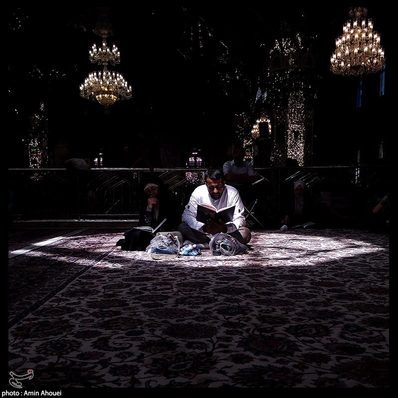 یک زوج در حرم علی بن موسی الرضا در حال زیارتنامه خوانی هستند.