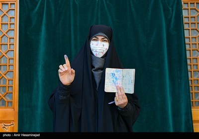 A woman in a medical mask posed for a picture after voting in Qom