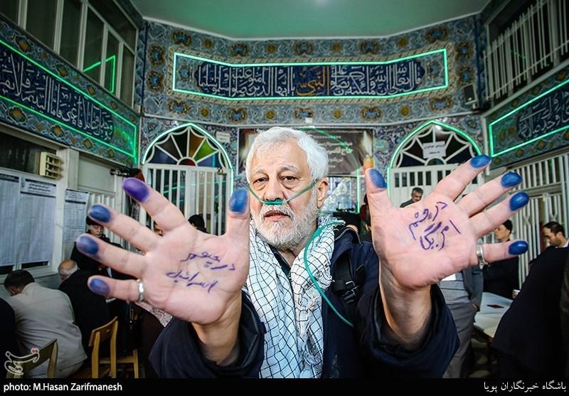 An elderly man poses after voting in the Narmak neighborhood of Tehran