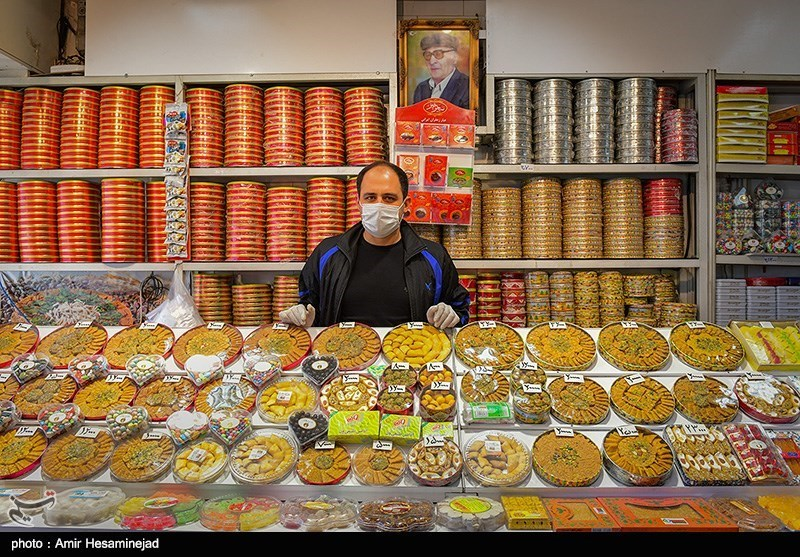 A shopkeeper in a face mask posed with sweets on March 18.