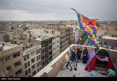 آقای تاجیک برای سرگرم کردن کودکان خود در روز سیزده به در برای آن ها بر بالای پشت بام چادر زده و در حال بالا بردن بادبادک است.